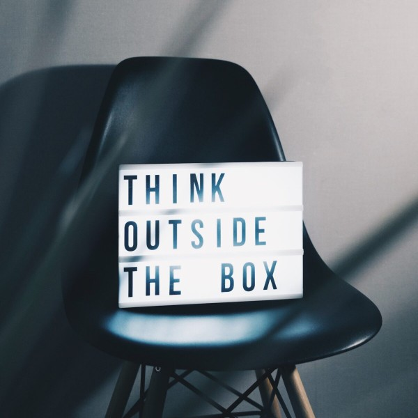 """Photograph of a chair with a sign that says """"Think outside the box"""""""
