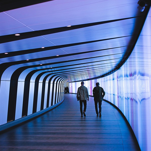 Two people walking in a dimly lighted futuristic hallway